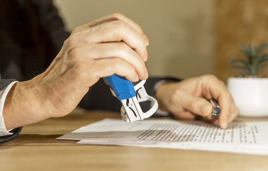 Man using self inking stamps on some documents